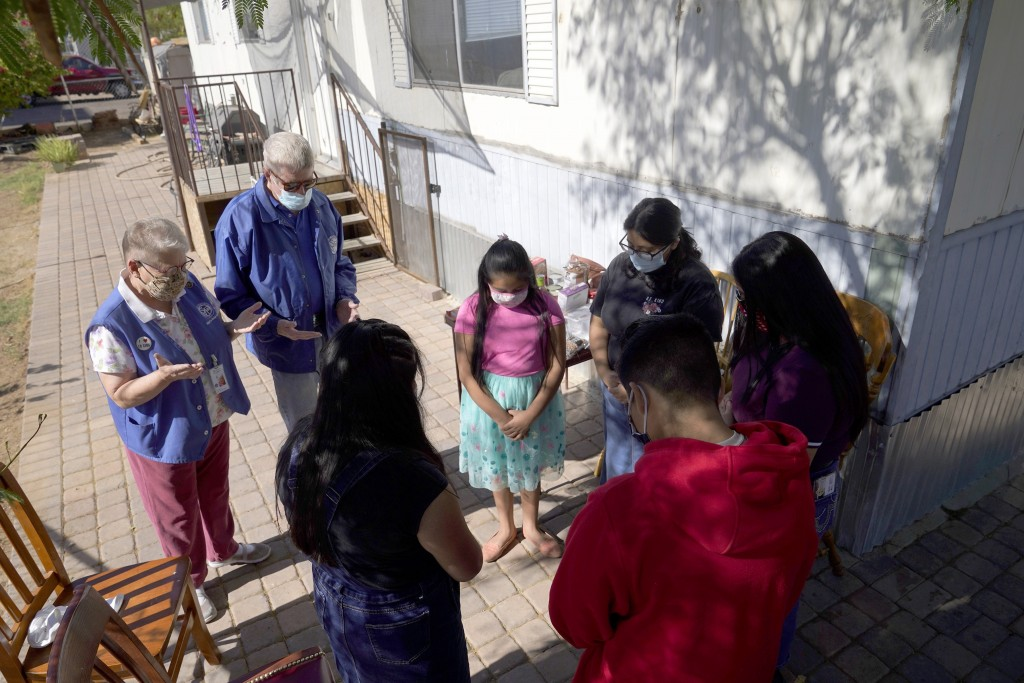 From left, St. Vincent de Paul volunteers Mary Ann Kneip and her husband, Pete Kneip, pray with Zeret Leocadio, 10; her sister, Areli, 9; her brother,...