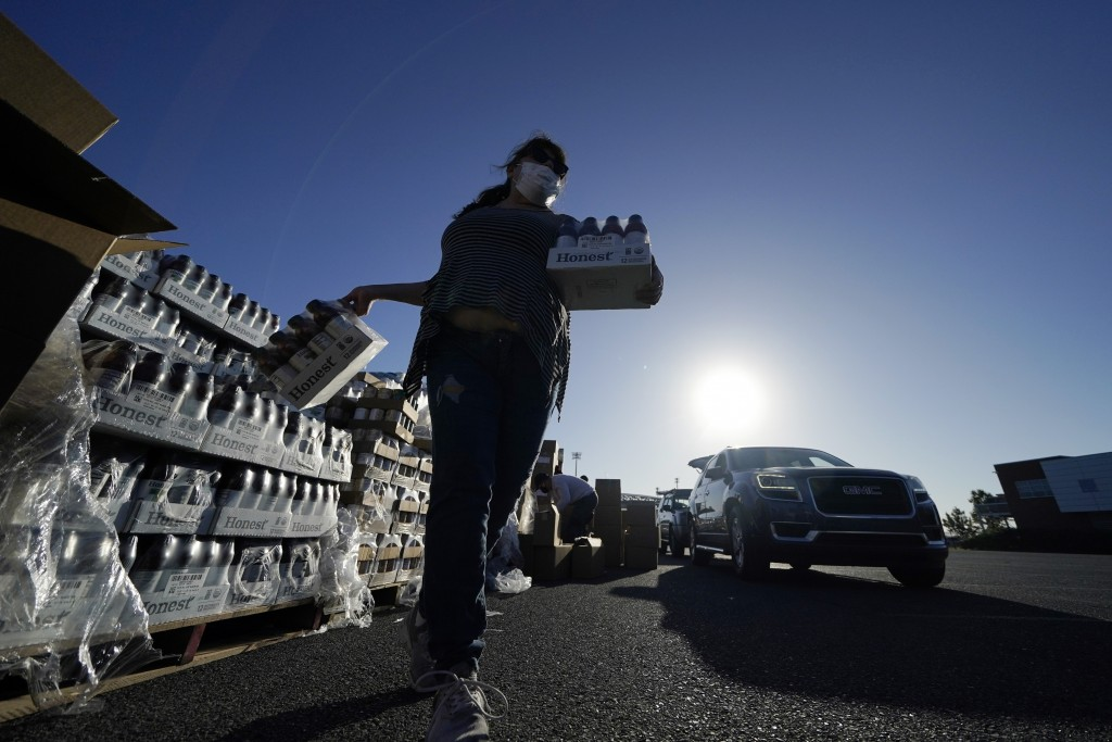Volunteers distribute food to people who waited in line in their cars overnight, at a food distribution point in Metairie, La., Thursday, Nov. 19, 202...