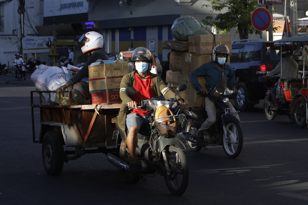 Motorcycle delivery riders wear face masks to curb the spread of the coronavirus transport goods in Phnom Penh, Cambodia, Tuesday, Dec. 8, 2020. Altho...
