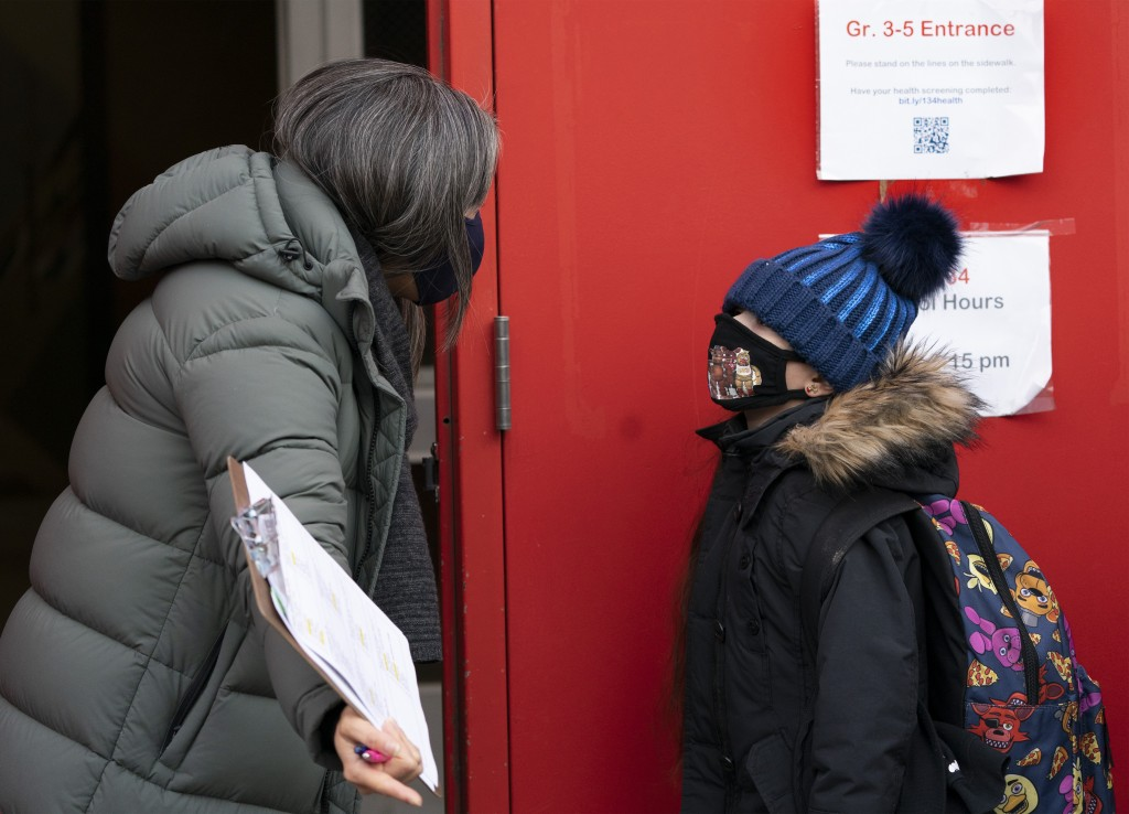 A school administrator, left, asks a student if his parents have completed a form granting permission for random COVID-19 testing as he arrives at P.S...