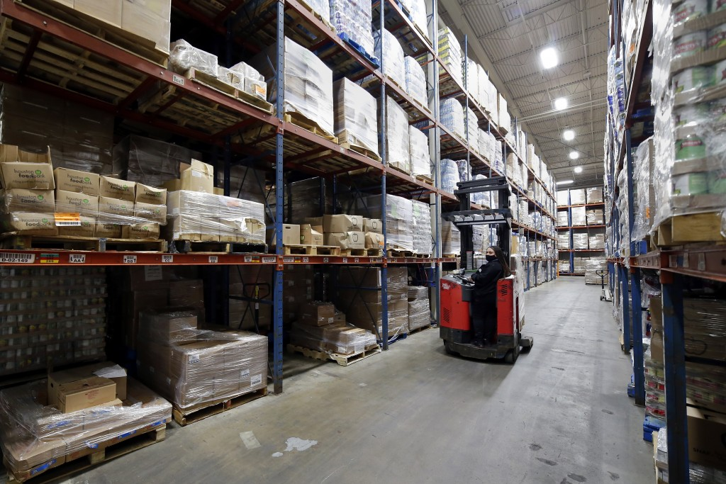 Fork lift driver Linda Rodriguez repositions pallets of boxed foods within the extensive warehouse at the Houston Food Bank Wednesday, Oct. 14, 2020, ...