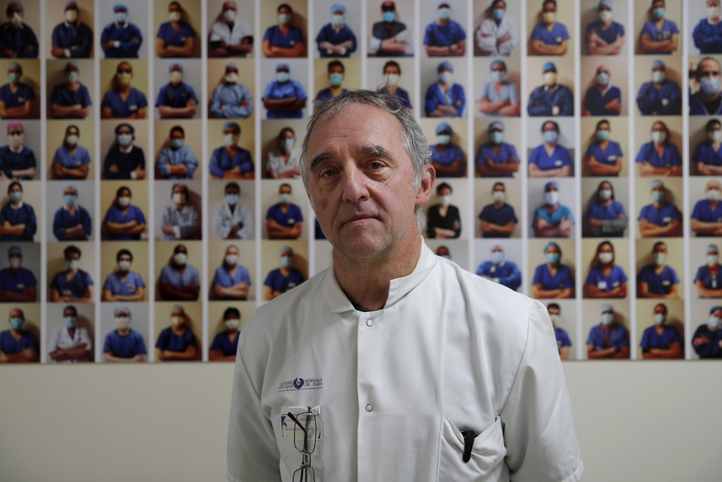 Dr. Philippe Montravers poses in front of a collection of portraits of medical staff at Bichat Hospital, AP-HP, in Paris, Wednesday, Dec. 2, 2020. One...