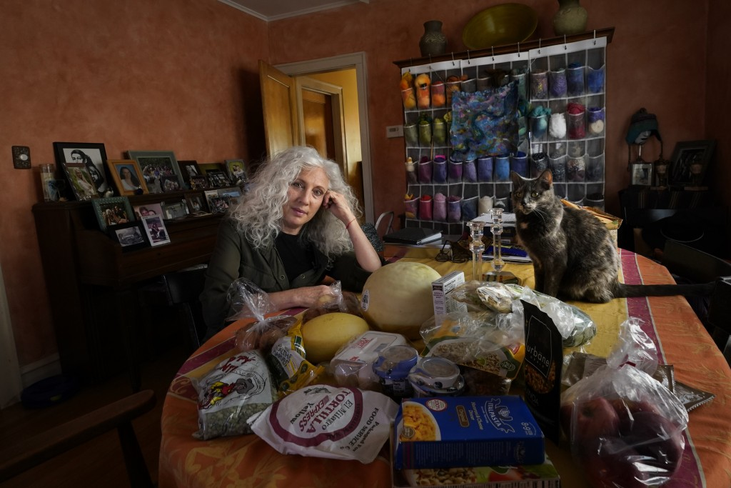 Phyllis Marder poses with her cat, Nellie, with food she recently obtained from a local food bank in the dining room of her home in Evanston, Ill., on...