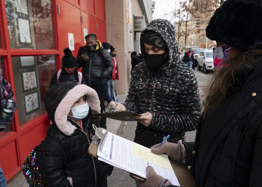 A parent, center, completes a form granting permission for random COVID-19 testing for students as he arrives with his daughter, left, at P.S. 134 Hen...