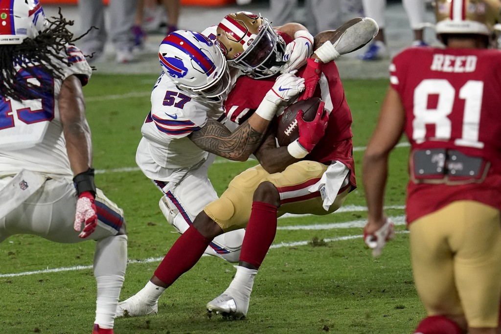 San Francisco 49ers running back Jeff Wilson (30) is hit by Buffalo Bills defensive end A.J. Epenesa (57) during the second half of an NFL football ga...