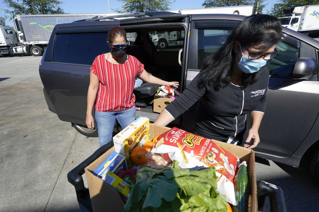 Johnna Nieves, left, opens her van as Idalia Nunez, right, of the Second Harvest Food Bank loads the vehicle with a weeks supply of food in Orlando, F...