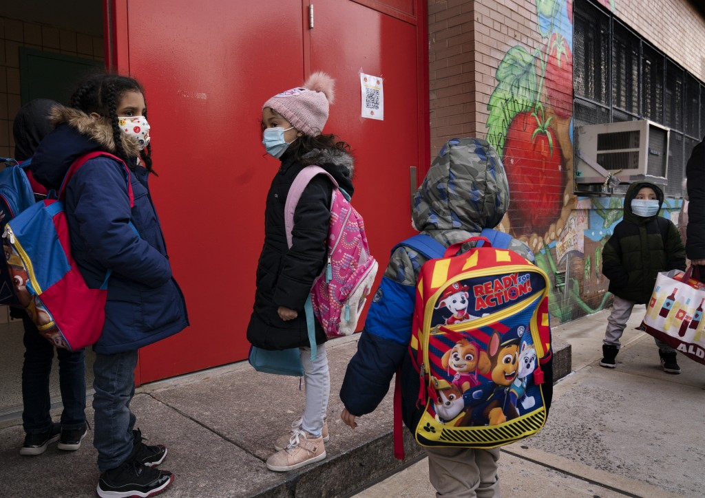 Students enter P.S. 134 Henrietta Szold Elementary School, Monday, Dec. 7, 2020, in New York. Public schools reopened for in-school learning Monday af...