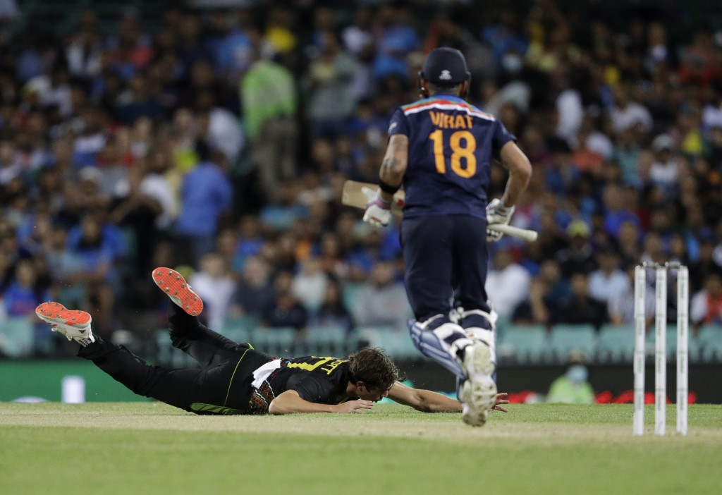 Australia's Sean Abbott, left, falls on the ground in an attempt to field the ball after a shot played by India's captain Virat Kohli, right, during t...