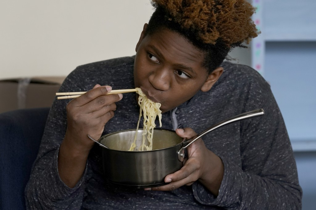 Nehemiah Powell, 14, watches TV and eats noodles Saturday, Nov. 21, 2020, following his virtual school gym workout at his home in Skokie, Ill. After h...