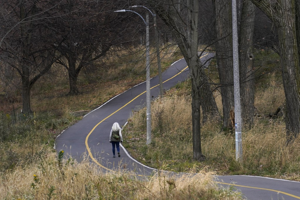 Phyllis Marder walks along a River Park bike trail Wednesday, Nov. 11, 2020, in Chicago. She'll be working as a coronavirus contract tracer for a near...