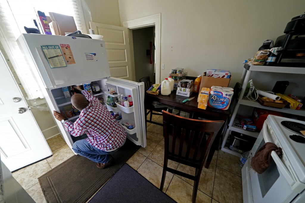Norman Butler unboxes food that he received at a food distribution point, in his apartment, after waiting in line overnight, in New Orleans, Thursday,...