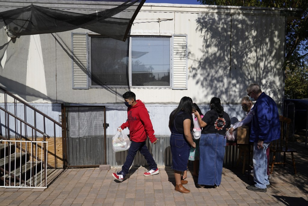 From left, Eliel Leocadio, 12, sisters Zeret, 10, Areli, 9, and their mother, Abigail Leocadio, bring food into their home after volunteers Mary Ann K...