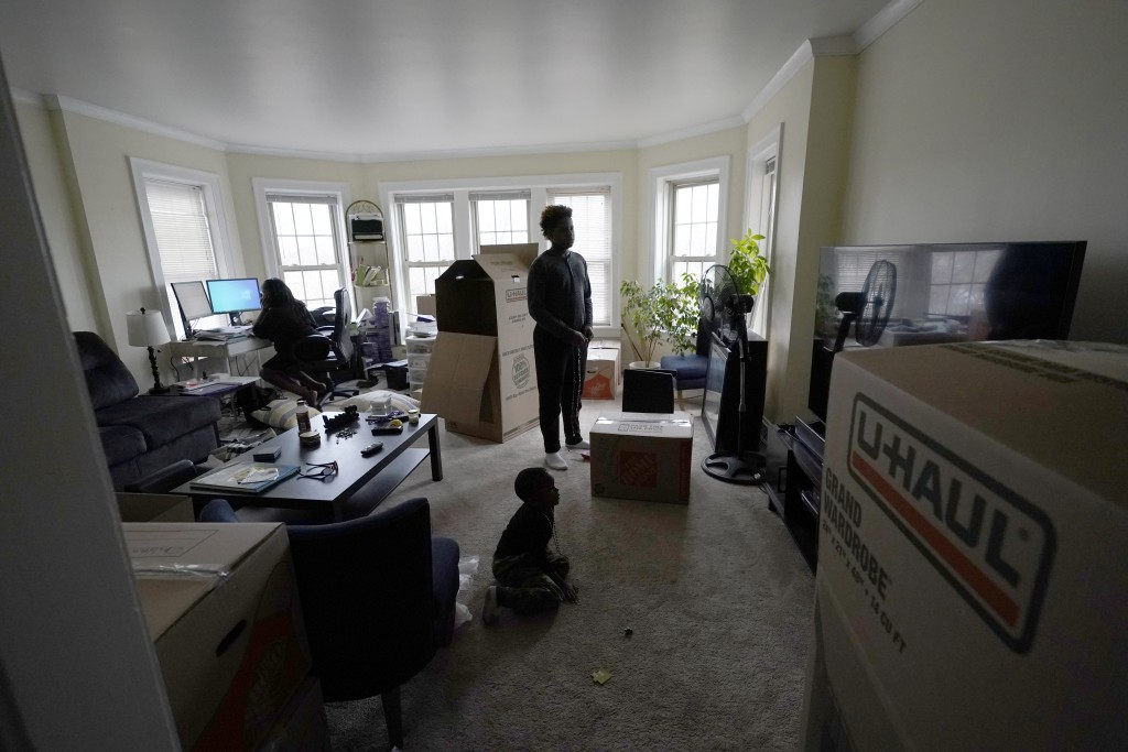 Briana Dominguez, left, continues to work remotely at a her job which will be eliminated at the end of December, as her sons Nehemiah Powell, 14, stan...