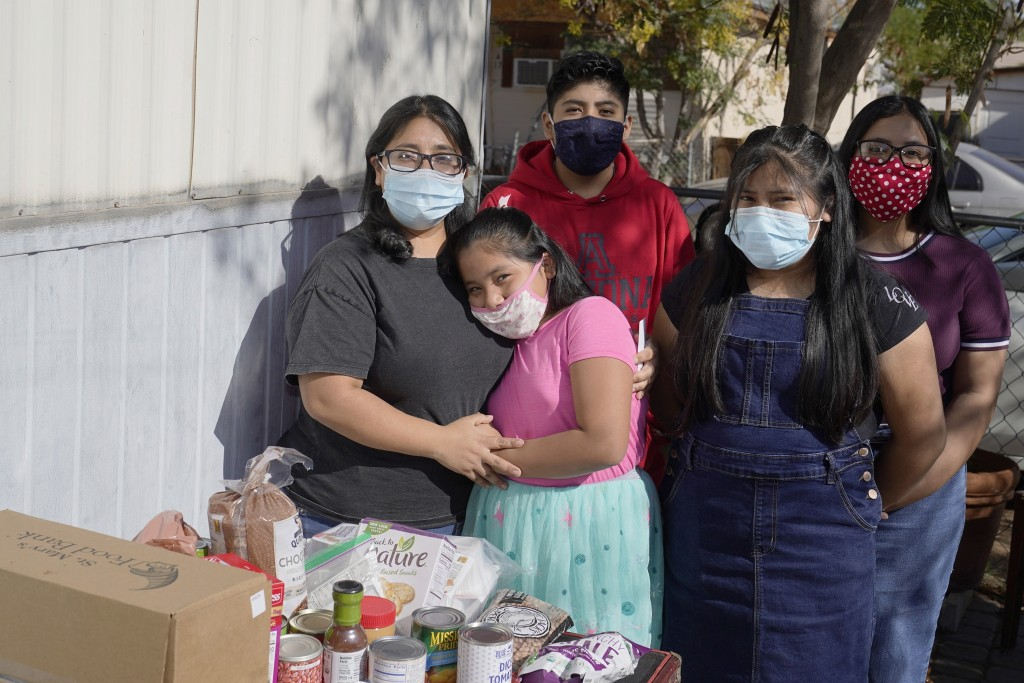 From left, Abigail Leocadio, stands with her children, Areli, 9, Eliel, 12, Zeret, 10, and Samai, 15, after a delivery from the Emmaus House food pant...