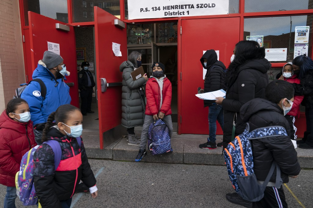 Students arrive at P.S. 134 Henrietta Szold Elementary School, Monday, Dec. 7, 2020, in New York. Public schools reopened for in-school learning Monda...