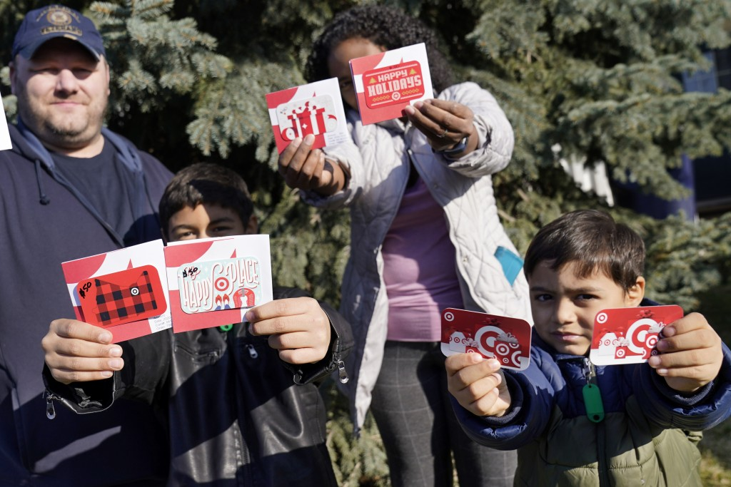 Sornic, left, and Gabriel hold gift cards received by their parents, Aaron and Sheyla Crawford, outside their Apple Valley, Minn., home on Saturday, N...