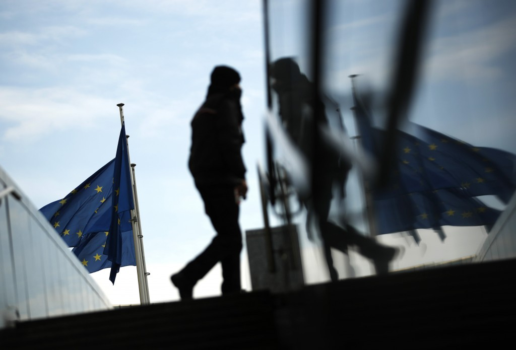 A pedestrian is reflected as they walk by EU flags outside EU headquarters in Brussels, Tuesday, Dec. 8, 2020. Britain and the European Union warned T...