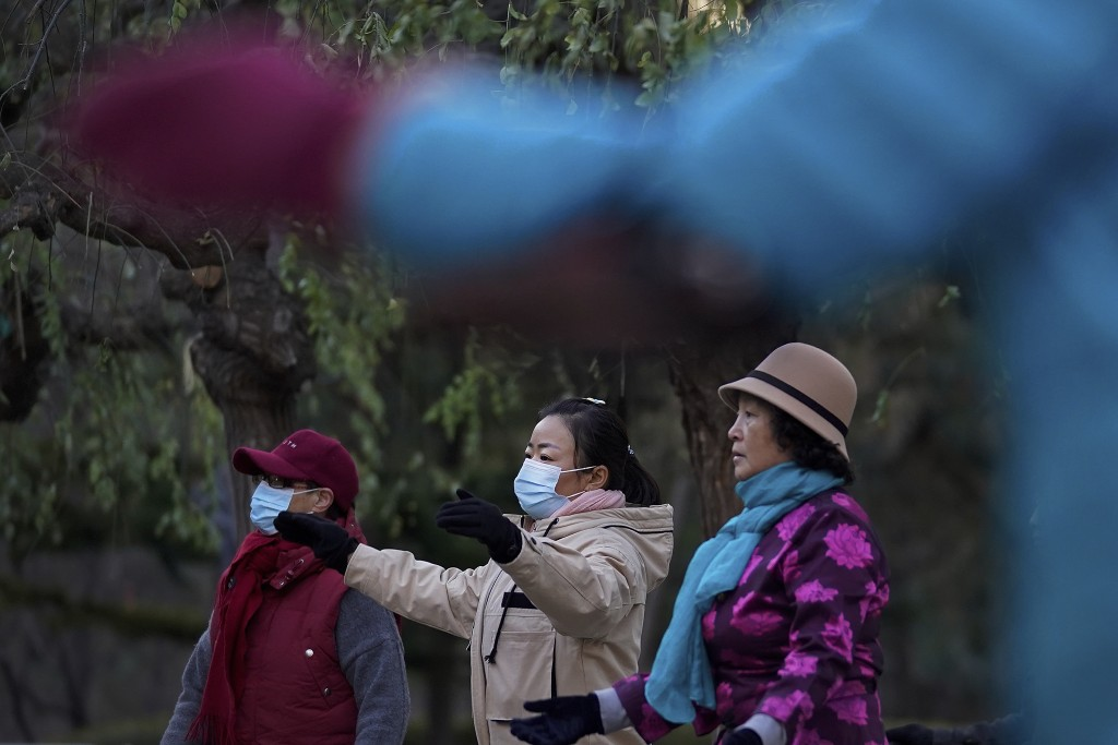 Women wearing face masks to help curb the spread of the coronavirus take part in a cultures dance with other participants at a public park in Beijing,...