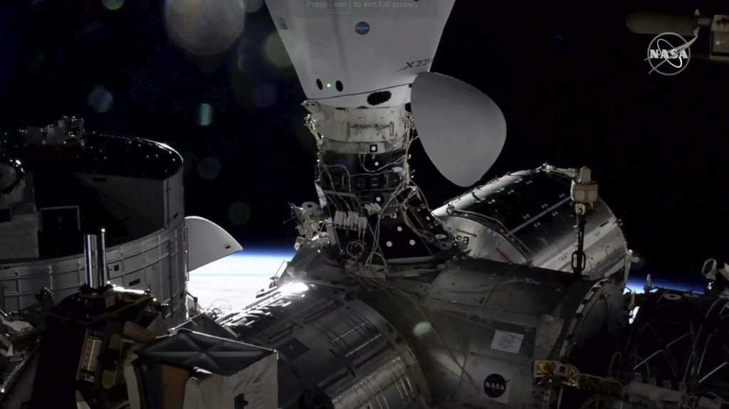 In this image taken from NASA TV the Dragon cargo capsule docks at the International Space Station, Monday, Dec. 7, 2020, alongside a Dragon crew caps...