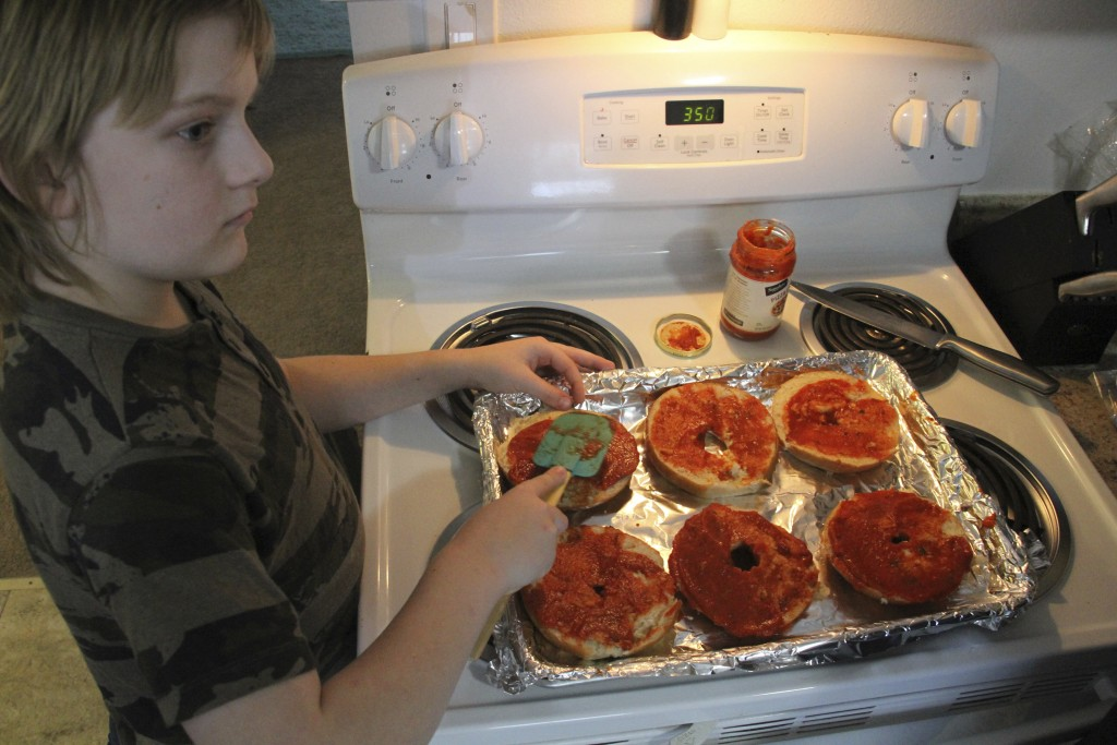 Jayden Messick, 9, helps his parents, Brian and Airis Messick, prepare lunch at their apartment in Anchorage, Alaska, on Wednesday, Nov. 11, 2020. The...