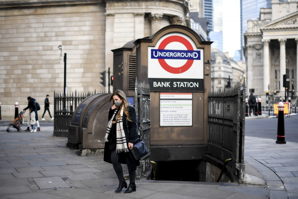 A woman wears a face mask as she steps out of Bank underground station, in London, Tuesday, Dec. 8, 2020.  The United Kingdom is beginning a mass vacc...