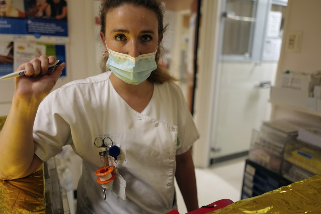 Medical staff member Alexandra Pichon Dignac pauses as Lolita Andela and Caroline Erganian, arrive on the eve of their surgery, at Bichat Hospital, AP...