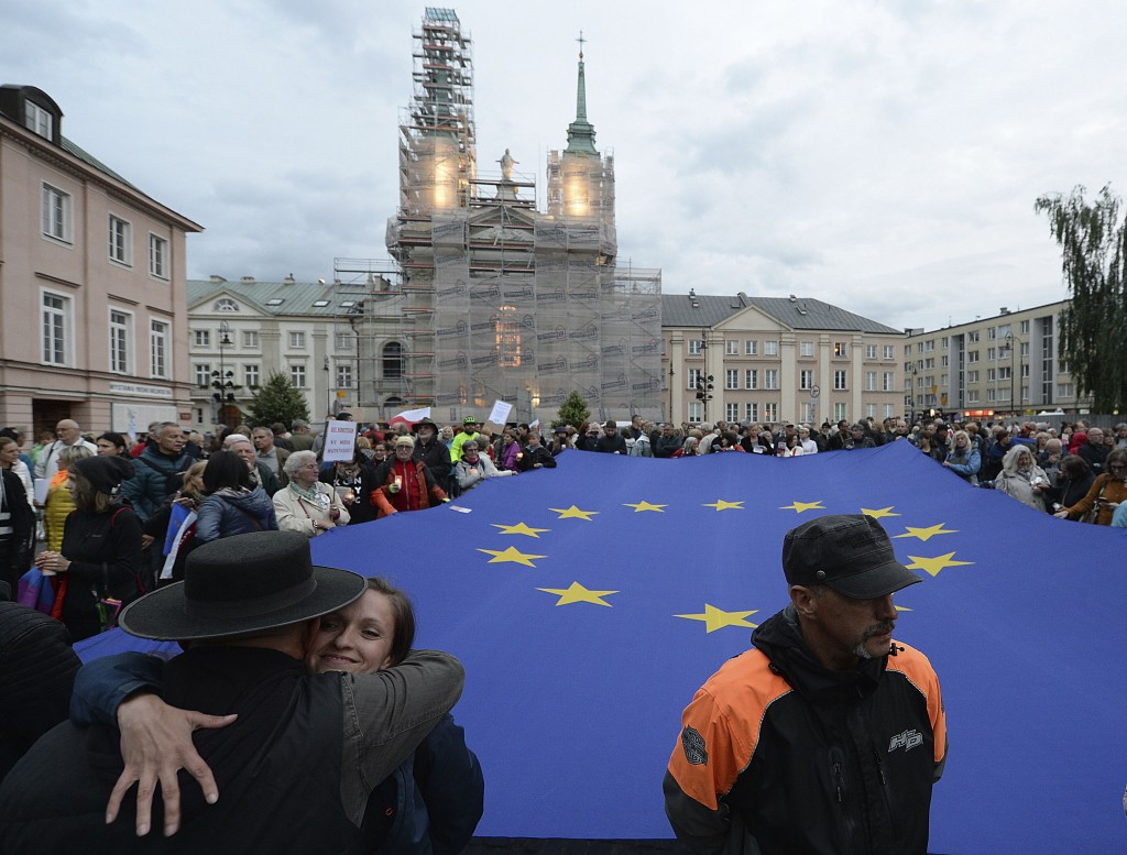 FILE - In this July 2, 2018 file photo, protesters carry an EU flag at an anti-government protest in Warsaw, Poland. Some Poles are afraid that a draw...