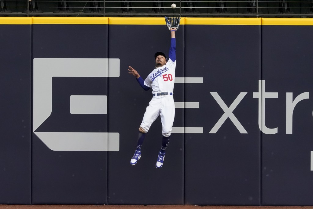 Los Angeles Dodgers right fielder Mookie Betts robs Atlanta Braves' Marcell Ozuna of a home during the fifth inning in Game 6 of a baseball National L...
