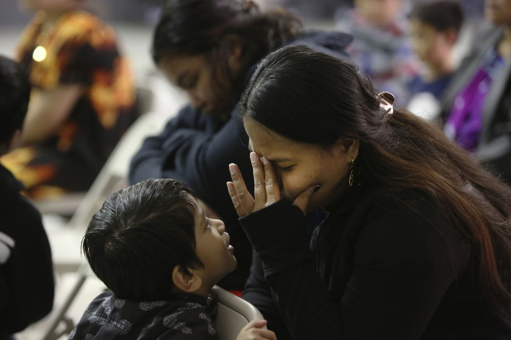 A young boy watches intently as Myuki, right, prays during services at The Living Water Noel Micronesian Christian Church, Sunday, Nov. 22, 2020, in N...