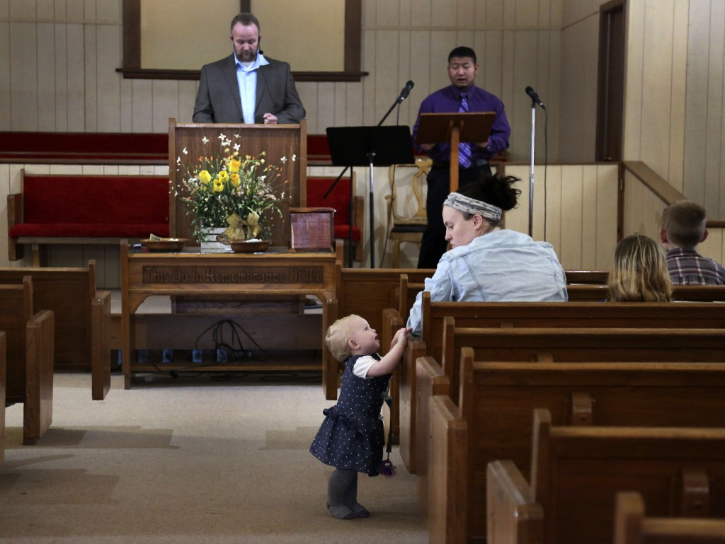 Alinia Rogers distracts her mother, Nicole Rogers, as Pastor Joshua Manning, left, of the Community Baptist Church, delivers a sermon on Sunday, Nov. ...