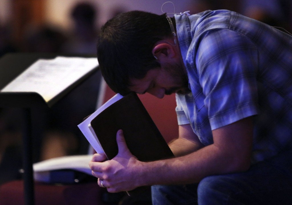Pastor Mike Leake, of Calvary of Neosho, a Southern Baptist church, rests his head on his Bible as he prays during service in Neosho, Mo., Sunday, Nov...