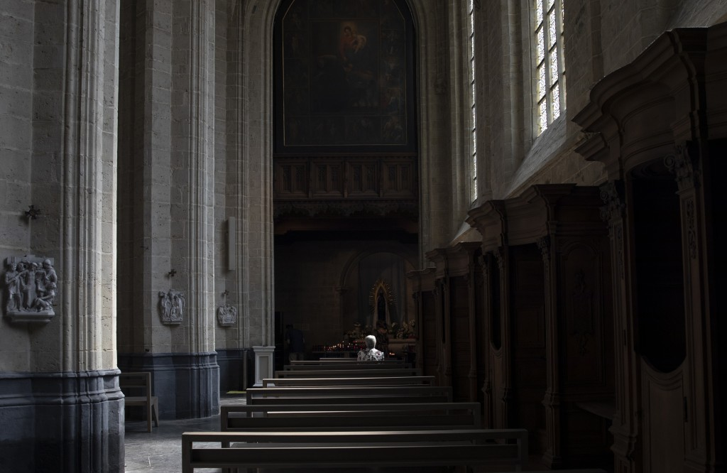 FILE - In this Wednesday, June 24, 2020 file photo, a woman prays at the Saint Martin Basilica in Halle, Belgium during a partial lockdown to prevent ...