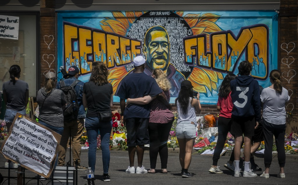 FILE - In this May 31, 2020 file photo, visitors make silent visits to organic memorial featuring a mural of George Floyd, near the spot where he died...