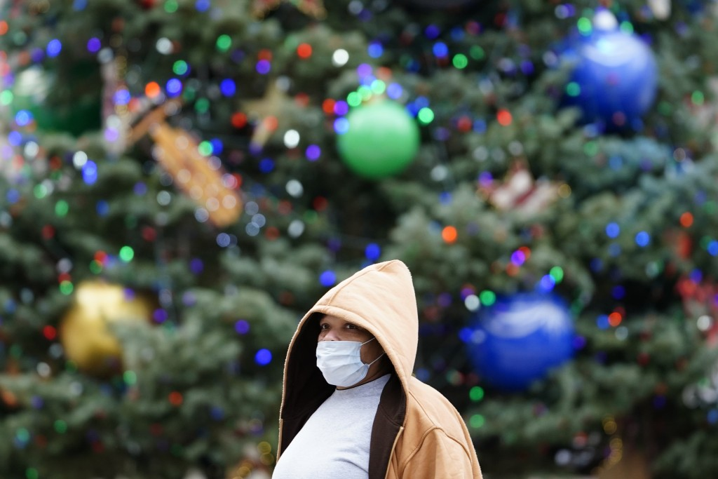 A person wearing a face mask to protect against the spread of the coronavirus walks past holiday decorations at City Hall, Tuesday, Dec. 8, 2020, in P...