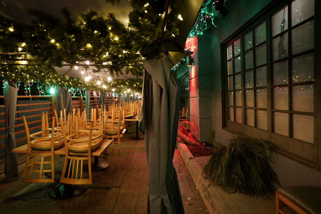 FILE - In this Monday, Dec. 7, 2020, file photo, chairs are stacked on tables in the closed outdoor dining area of a restaurant in Rowland Heights, Ca...