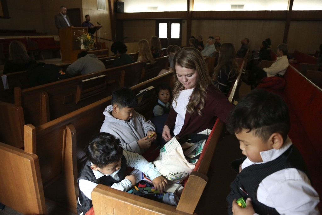 Hannah Snow, a congregant and singer for the Community Baptist Church, gives toys to young parishioners during services, Sunday, Nov. 22, 2020, in Noe...