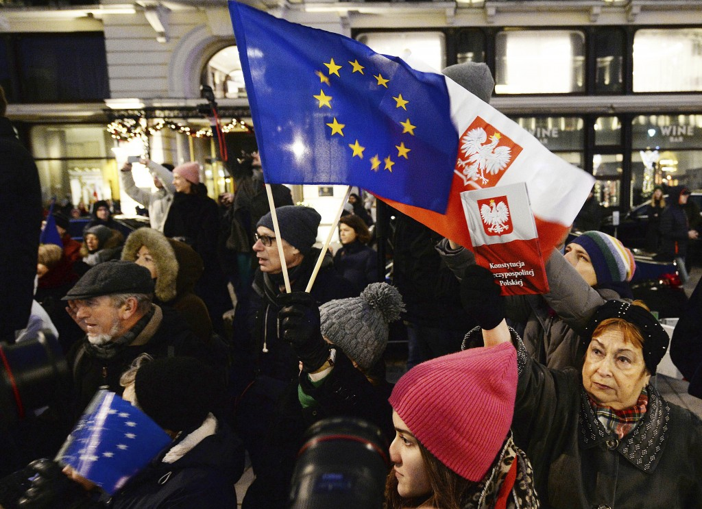 FILE - In this  Jan. 11, 2020 file photo, protesters carry an EU flag at an anti-government protest in Warsaw, Poland. Some Poles are afraid that a dr...