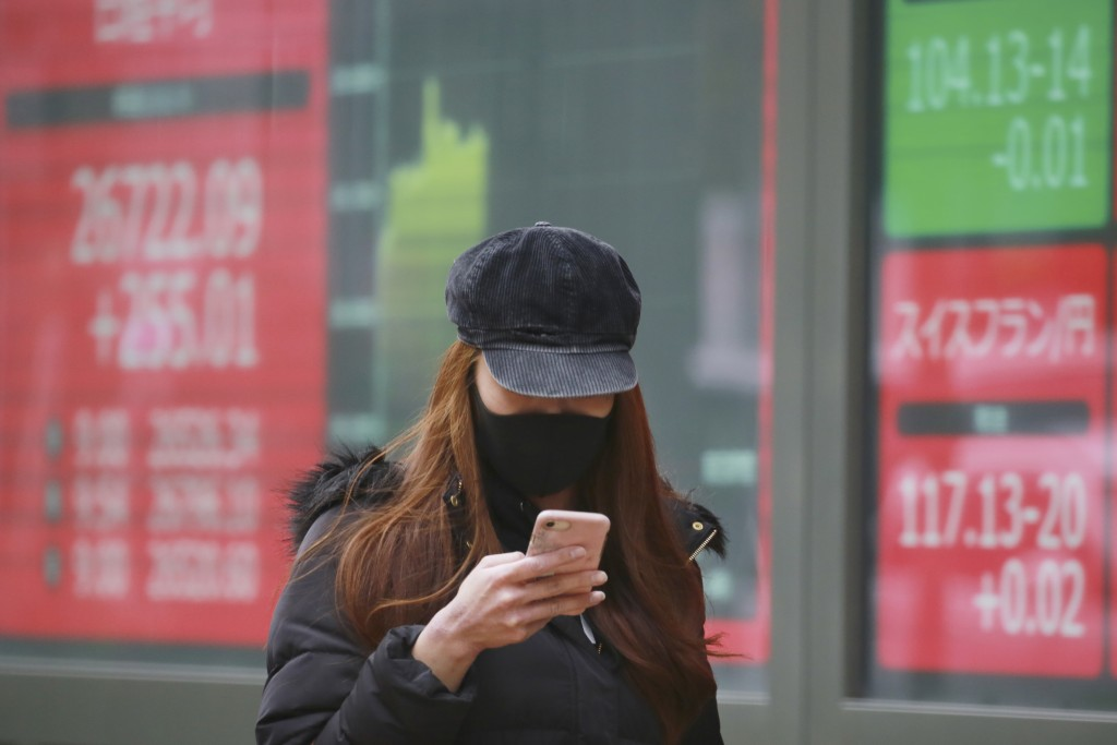 A woman wearing a face mask to help curb the spread of the coronavirus walks by an electronic stock board of a securities firm in Tokyo, Wednesday, De...