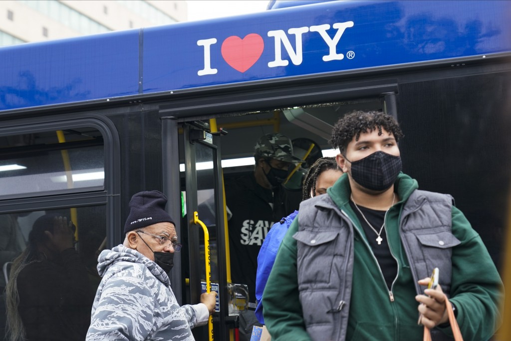 People wearing protective masks exit a bus at the Fordham Metro North station Thursday, Oct. 22, 2020, in New York.  As the coronavirus rages across t...
