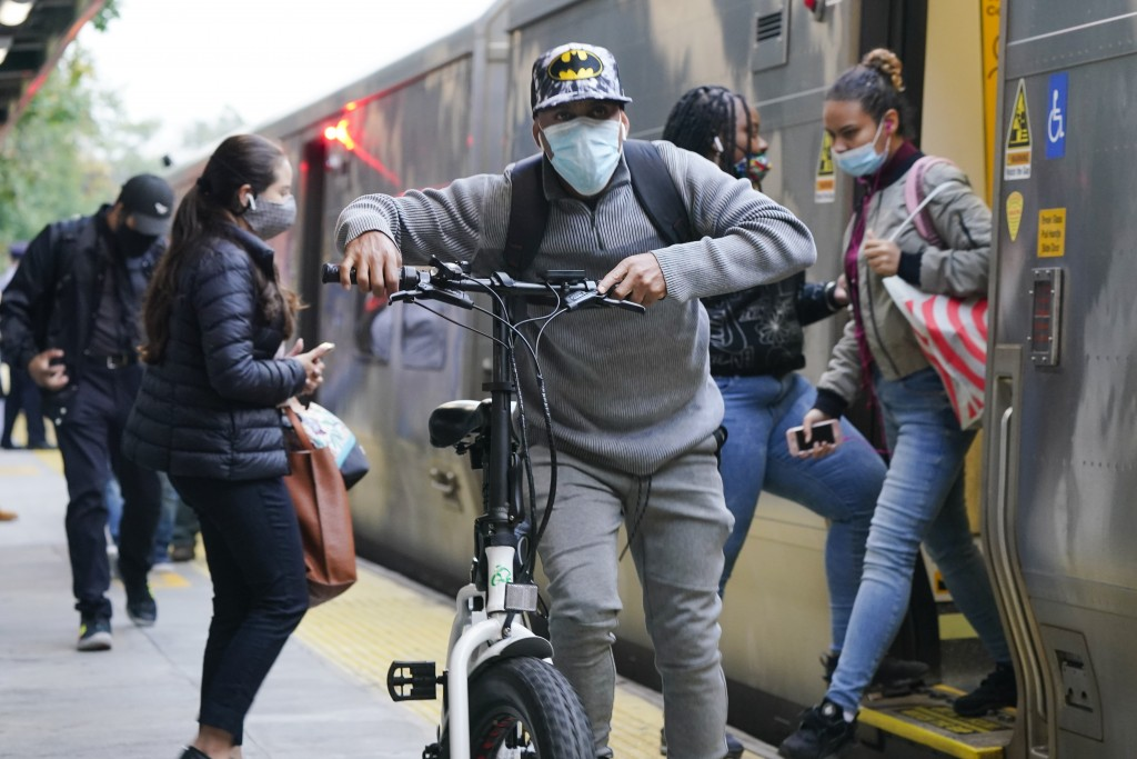 People enter and exit a train at the Fordham Metro North station Thursday, Oct. 22, 2020, in New York.  As the coronavirus rages across the U.S., groc...