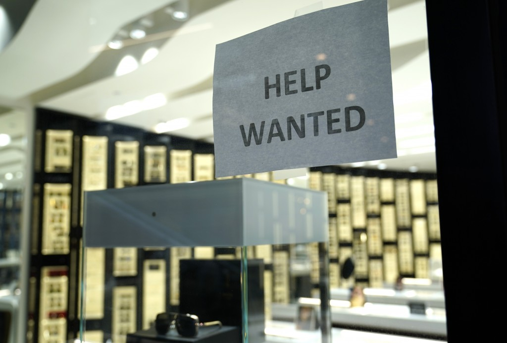 A Help Wanted sign is posted at a Designer Eyes store at Brickell City Centre, Friday, Nov. 6, 2020, in Miami. The number of people applying for unemp...
