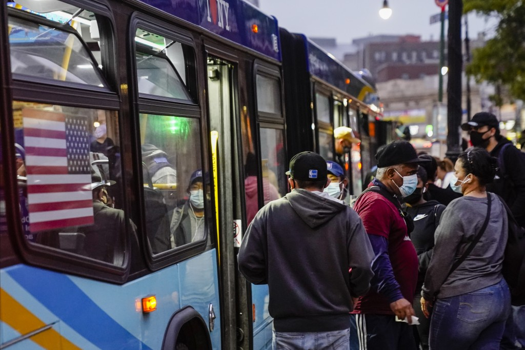 Patrons board exit and enter a bus at the Fordham Metro North station Thursday, Oct. 22, 2020, in New York.  As the coronavirus rages across the U.S.,...