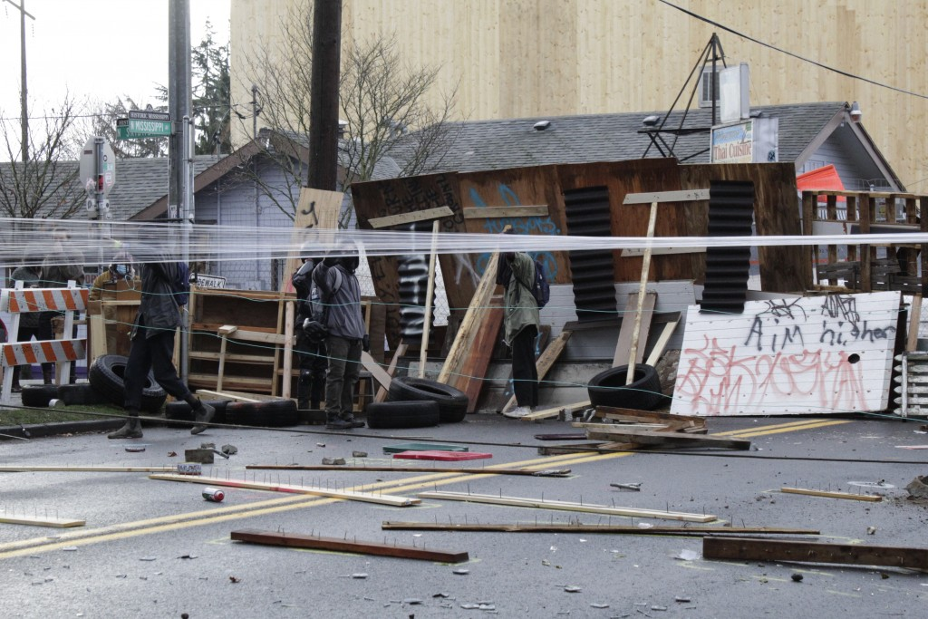 Protesters stand behind barricades at their encampment outside a home in Portland, Ore., on Wednesday, Dec. 9, 2020. Makeshift barricades erected by p...