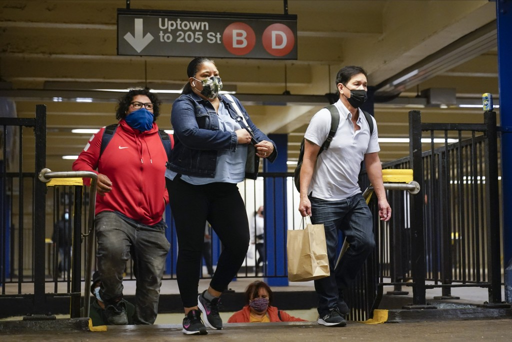 People wearing protective masks exit the Fordham Road subway station Thursday, Oct. 22, 2020, in New York.  As the coronavirus rages across the U.S., ...