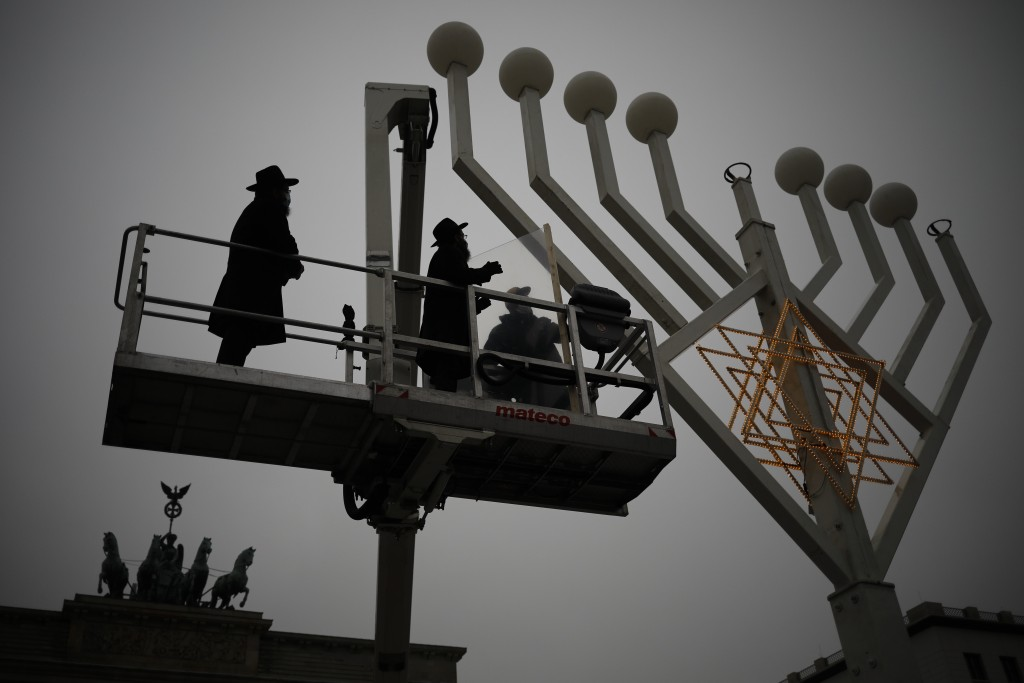 Rabbi Yehuda Teichtal, left, and Rabbi Segal Shmoel, second from left, inspect a giant Hanukkah Menorah, set up by the Jewish Chabad Educational Cente...