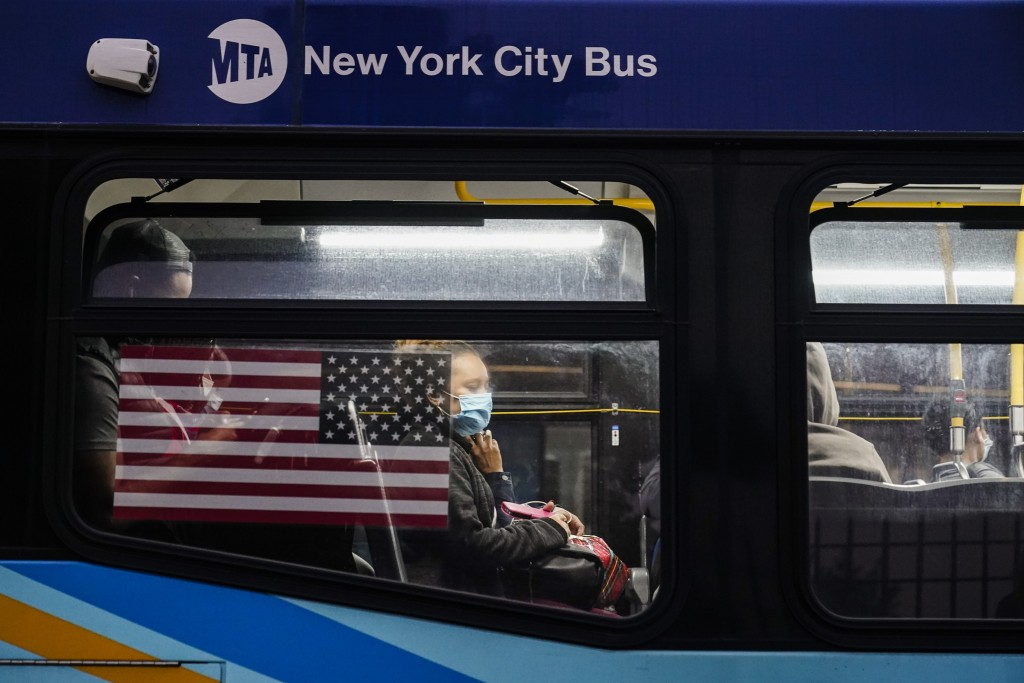 People wear protective masks during the coronavirus pandemic while on a bus at the Fordham Metro North station Thursday, Oct. 22, 2020, in New York.  ...