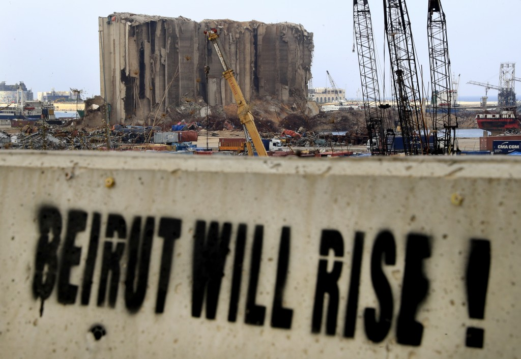A slogan is painted on a barrier in front of towering grain silos gutted in the massive August explosion at the Beirut port that claimed the lives of ...