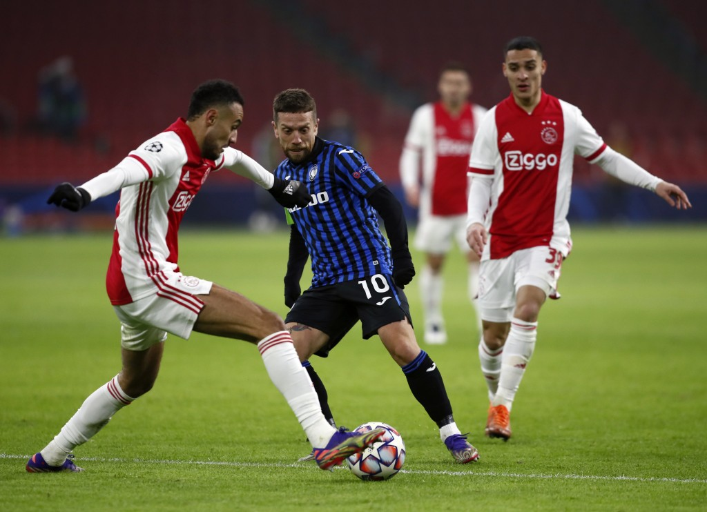 Ajax's Noussair Mazraoui, left, duels for the ball with Atalanta's Papu Gomez, centre, during the group D Champions League soccer match between Ajax a...