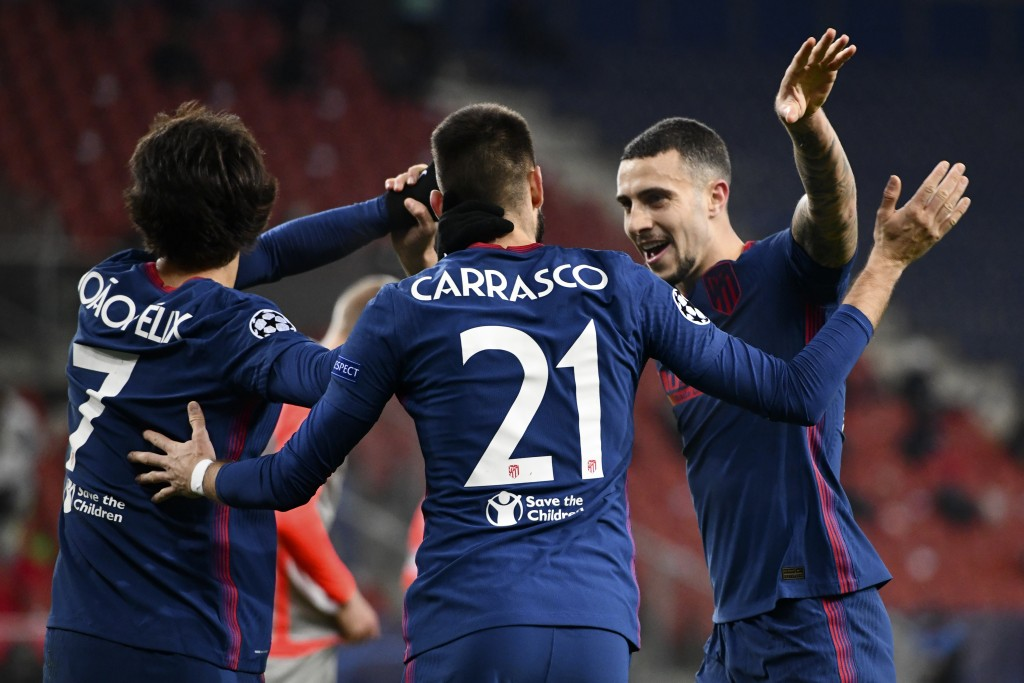 Atletico Madrid's Yannick Carrasco celebrates with Joao Felix, left, and Mario Hermoso, right, after scoring their side's second goal during the Champ...