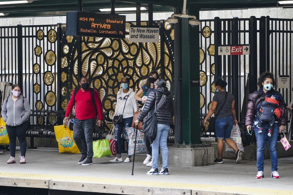 People wearing protective masks during the coronavirus pandemic wait for a train at the Fordham Metro North station Thursday, Oct. 22, 2020, in New Yo...